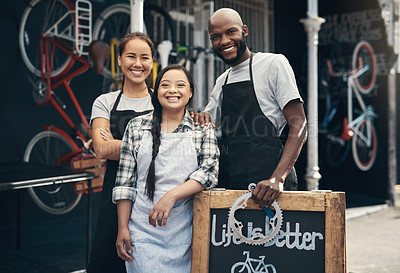 Buy stock photo Portrait of three young working workers standing behind a bicycle repair sign outside