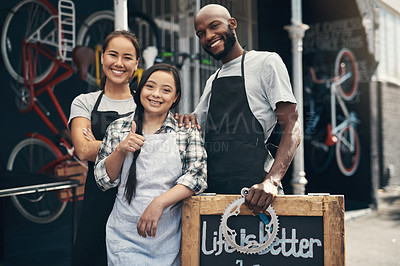 Buy stock photo Portrait of three young workers standing behind a bicycle repair sign outside