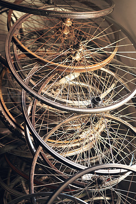 Buy stock photo Shot of bicycle wheel frames stacked on the floor
