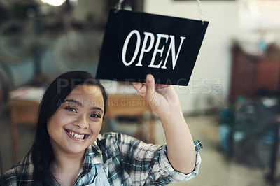 Buy stock photo Portrait of a young woman turning an open sign at work