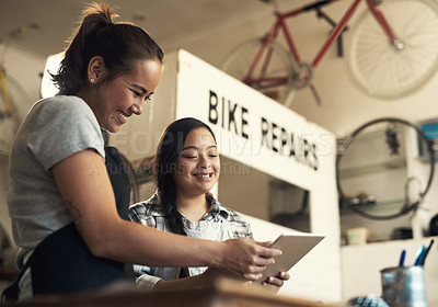 Buy stock photo Shot of two young women using a digital tablet at work