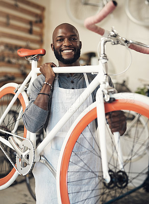 Buy stock photo Portrait of a young man lifting a bicycle up at work