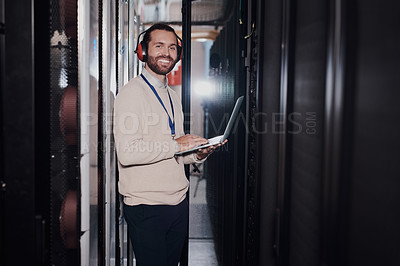 Buy stock photo Portrait of a young handsome man wearing headphones and using a laptop at work in a server room
