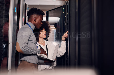Buy stock photo Shot of two young workers using a laptop in a server room at work