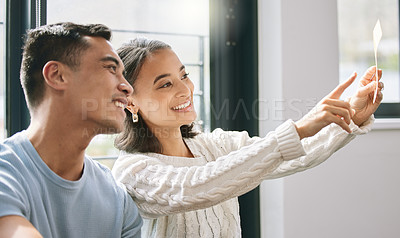 Buy stock photo Shot of a young couple sitting together and planning the interior design of their new home