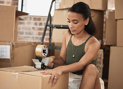 Buy stock photo Shot of a young woman packing up to move in a room at home
