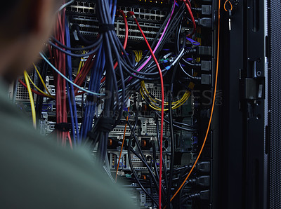 Buy stock photo Cropped shot of an unrecognizable male IT support agent working in a dark network server room
