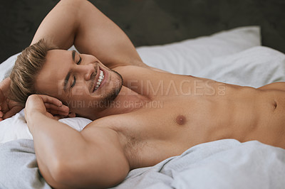 Buy stock photo Cropped shot of a handsome and muscular young man lying in his bed at home