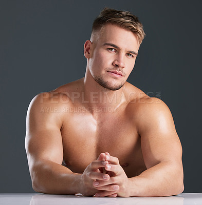Buy stock photo Studio portrait of a handsome and hunky young man posing in studio against a gray background