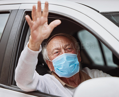 Buy stock photo Shot of a senior man waving while sitting in his car at a drive through vaccination site