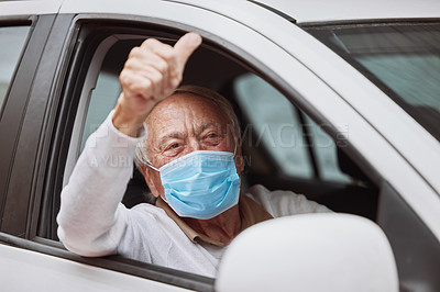 Buy stock photo Shot of a senior man showing a thumbs up in his car at a drive through vaccination site