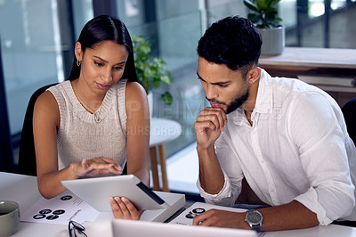 Buy stock photo Shot of two work colleagues working together while using a digital tablet