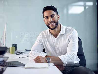 Buy stock photo Shot of a young businessman sitting at his work desk
