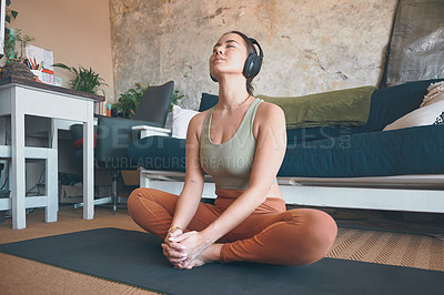 Buy stock photo Shot of a young woman wearing headphones while exercising at home