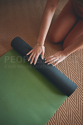 Buy stock photo High angle shot of an unrecognisable woman rolling a yoga mat while exercising at home