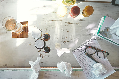 Buy stock photo High angle shot of medication, tissues a notepad and glasses on a table at home
