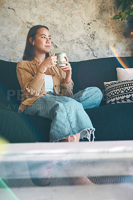 Buy stock photo Shot of a young woman having coffee and relaxing on the sofa at home