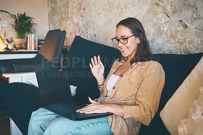 Buy stock photo Shot of a young woman using a laptop to make a video call on the sofa at home