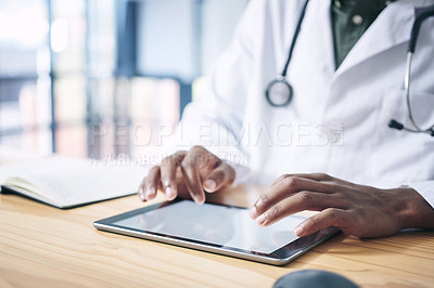 Buy stock photo Cropped shot of an unrecognizable doctor sitting alone in his office at the clinic and using his digital tablet