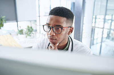 Buy stock photo Shot of a young doctor sitting alone in his office at the clinic and looking contemplative while using his computer