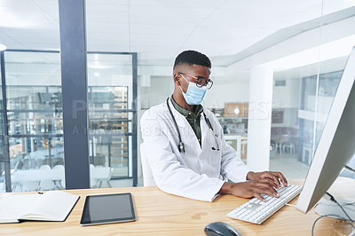 Buy stock photo Shot of a young doctor wearing a mask and sitting in his office at the clinic while using a computer