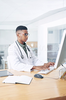 Buy stock photo Shot of a handsome young doctor sitting alone in his office at the clinic and using his computer