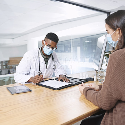 Buy stock photo Shot of a young doctor sitting with his patient and wearing a mask while writing a prescription during a consultation