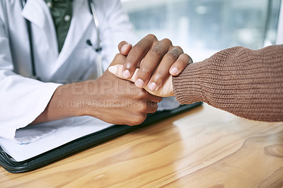 Buy stock photo Cropped shot of an unrecognizable doctor sitting with his patient and comforting her during a consultation in the clinic