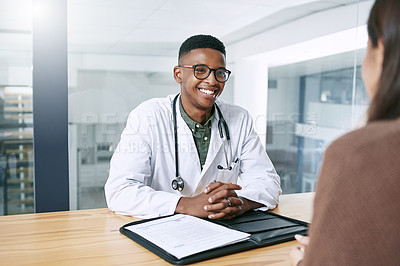 Buy stock photo Shot of a handsome young doctor sitting with his patient during a consultation in the clinic
