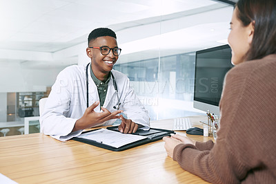 Buy stock photo Shot of a handsome doctor sitting with his patient and explaining her diagnosis during a consultation in the clinic