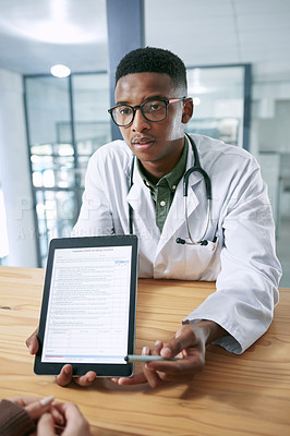 Buy stock photo Shot of a young doctor sitting with his patient and using a digital tablet during a consultation in the clinic