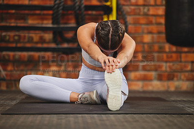 Buy stock photo Shot of a young unrecognizable woman stretching while exercising at the gym