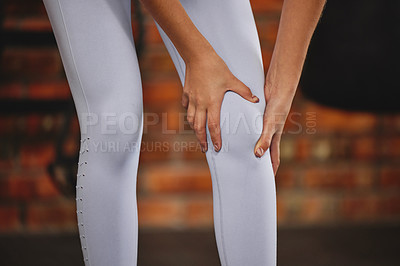 Buy stock photo Shot of an unrecognizable young woman holding her knee while exercising at the gym