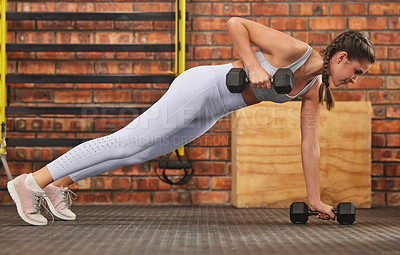 Buy stock photo Shot of a young woman showing off her core strength in the planking position while lifting weights at the gym