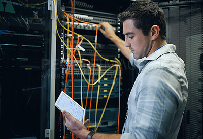 Buy stock photo Cropped shot of a handsome young male programmer working on a tablet in a server room