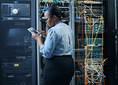 Buy stock photo Rearview shot of an attractive female programmer working on a tablet in a server room