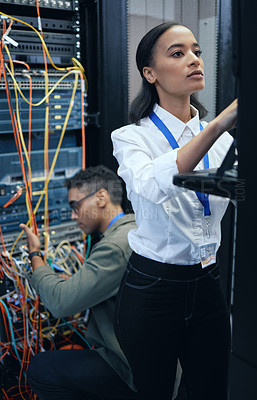 Buy stock photo Cropped shot of two young computer programmers working together in a server room