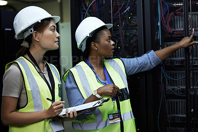 Buy stock photo Cropped shot of two attractive female programmers working in a server room