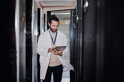 Buy stock photo Shot of a young man using a digital tablet in a server room at work