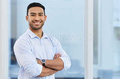 Buy stock photo Shot of a handsome young businessman standing alone in his office with his arms folded