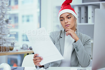 Buy stock photo Shot of a concerned young woman doing some paperwork at the office