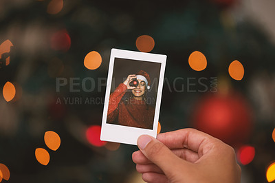 Buy stock photo Shot of an unrecognisable person holding a photo of a young woman celebrating Christmas