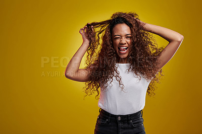 Buy stock photo Studio portrait of a young woman sticking out her tongue against a yellow background
