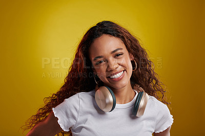 Buy stock photo Studio portrait of a young woman wearing headphones against a yellow background