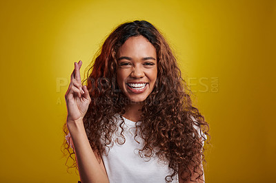 Buy stock photo Studio portrait of a young woman posing with her fingers crossed against a yellow background