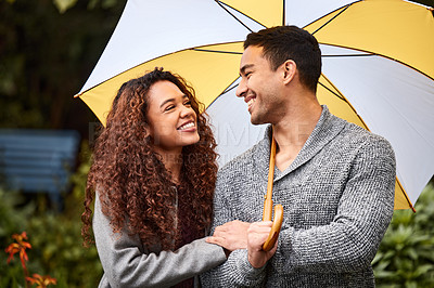 Buy stock photo Shot of a young couple standing in the rain with an umbrella