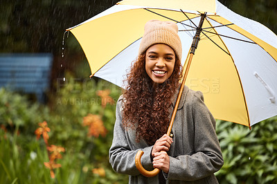 Buy stock photo Shot of a young woman standing in the rain with an umbrella