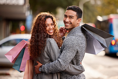 Buy stock photo Cropped portrait of an affectionate young couple enjoying a shopping spree in the city