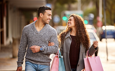 Buy stock photo Cropped shot of an affectionate young couple enjoying a shopping spree in the city