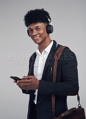 Buy stock photo Studio shot of a young businessman using a smartphone and headphones against a grey background